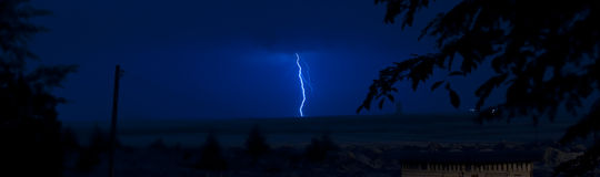 Lightning strikes over the ocean at night Stock Image