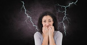 Lightning strikes and scared afraid woman biting nails. Digital composite of Lightning strikes and scared afraid woman biting nails Royalty Free Stock Photo