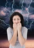 Lightning strikes and scared afraid woman biting nails. Digital composite of Lightning strikes and scared afraid woman biting nails stock photo