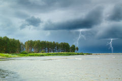 Lightning. summer storm coming ashore. the waves beating against Stock Image