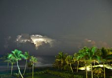 Lightning takes over the ocean horizon as a storm rages off the shoreline stock photography