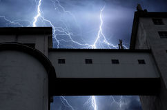 Lightning and thunder on stormy summer night over factory. Building stock photo