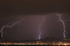 Lightning Thunderstorm. Over the city. Striking mountains and city lights Royalty Free Stock Photo
