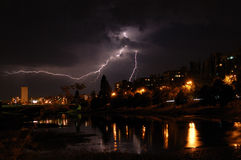 Lightning and thunderstorm. In the city with reflection in water of river royalty free stock image