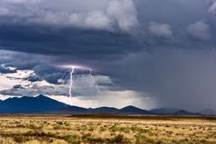 Lightning and thunderstorm. Lightning striking a mountain in a thunderstorm Royalty Free Stock Photos