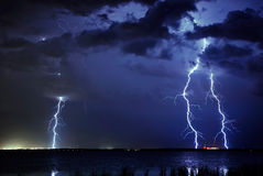 Lightning Triple. 3 lightning bolts striking  the ground reflected over a lake Stock Photos