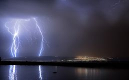 Lightnings. Image of night calm lake with big lightnings and a city lights on background Stock Photo