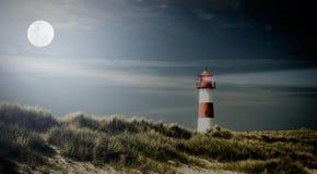 Lightouse sulla duna sulla sera Immagine Stock