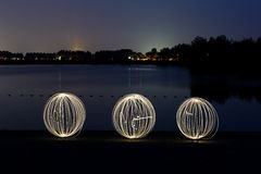 Lightpainting with orbs. 3 orbs, created with lightpainting and steel wool swinging in the sky. In the background you can see the little town of Elst, in the Royalty Free Stock Photography
