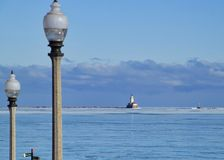 Lightpost in foreground with cloudscape over horizon of Lake Michigan on a freezing January morning with frozen lake Stock Photography