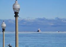 Lightpost i förgrund med cloudscape över horisont av Lake Michigan på en frysa Januari morgon med den djupfrysta sjön arkivbild