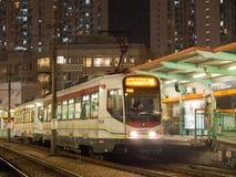 Lightrail en mooie post in Tin Shui Wai bij nacht stock afbeelding