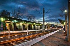 Lightrail post bij zonsondergang met sporen en lichten Persoon op ben stock foto