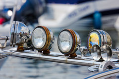 Lights. Four chrome motorboat flood lights on the rig and horn. Front view Royalty Free Stock Photos