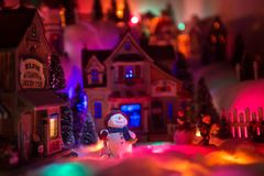 Holiday spirits of a snowman in Christmas times. Lights from above shines on happy face of snowman who stands in the middle of a miniature marketplace town royalty free stock photo
