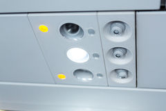 Lights, air condition  signs panel above the seat on plane Stock Photo