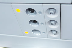 Lights, air condition  signs panel above the seat on plane Royalty Free Stock Photos