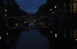 Lights on arched bridges are reflected in the water of Amsterdam canal at night. The lights of arched bridges on an Amsterdam canal are reflected in the water to Royalty Free Stock Image
