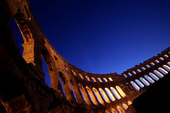 Lights through the arches of the amphitheatre in P Stock Images
