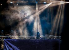 Lights beams on stage, smoke and young woman Dj playing music at Summer Night Festival. Fun, youth, entertainment and fest concept stock image