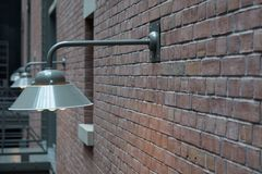 Lights on a brick wall 2. A row of metal lights on a brick wall Royalty Free Stock Photos
