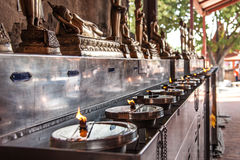 Lights of Buddhist oil candles at the temple. In Thailand Stock Photography