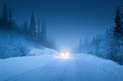 Lights of car and winter road Royalty Free Stock Photos