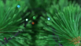 Lights of Christmas pine tree out of focus. Colorful garland lights are sparkling on the background. Red, blue, and yellow electric lights turning on and off stock video footage