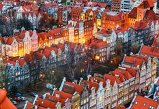Lights coming alive along a red roofed neighbourhood. Gdansk houses with red roofs at dusk as the lights are coming on stock photos