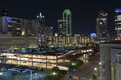 Lights of the Dallas skyline beyond a lit up parking garage Royalty Free Stock Photography