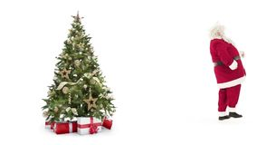 Lights decorated xmas tree with gift boxes and Santa Claus entering,waving and exiting on white background with text stock footage