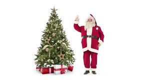 Lights decorated xmas tree with gift boxes and Santa Claus waving off on white background with text space to place logo stock footage