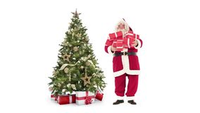 Lights decorated xmas tree and Santa Claus holding gift boxes on white background with text space to place logo or copy stock footage