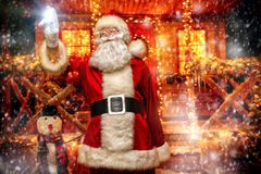 Lights and decorations for christmas. Portrait of surprised Santa Claus in the courtyard of his house decorated with Christmas lights. Christmas and New Year royalty free stock images