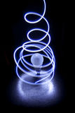 Lights encircling a bulb. Stream of light encircling a light bulb, against a black background Stock Photo