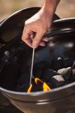 Lights Fire in a BBQ. The man kindles a match fire on a grill Royalty Free Stock Images