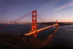 Lights illuminate the Golden Gate Bridge at twilight San Francisco. Lights illuminate the Golden Gate Bridge and city skyline at twilight in San Francisco aerial stock images