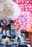Lights and lanterns in the night. Bokeh Wedding Banquet. The chairs and round table for guests.