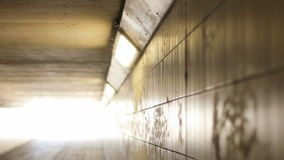 Lights Leading to Light at the end of an Empty Tunnel Pan Right. Medium long high angle shallow depth of field tracking slider shot panning right of a line of stock footage