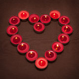 Lights of love. Red candles arranged in the shape of heart Stock Photos