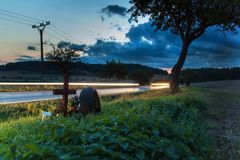 Lights of moving cars on a rural road. Evening in the place of a fatal accident. Place a car accident at the crossroads. Lights of moving cars on a rural road stock photography