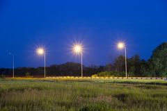 Lights near highway. Night scene. Lights of lanterns near highway. Night scene. Grass in a field at front plan. Trees in woodland belt at background. Bump stop royalty free stock photography