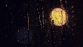 The lights of the night city. Misted glass. Liquid raindrops on the window. Sadness and sad mood background.