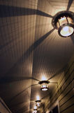 Lights & Shadows. Row of circular lights cast shadows upon ceiling stock image