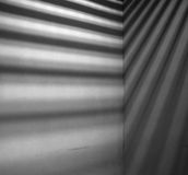 Lights and shadows falling on corner of concrete wall. Minimalist image of lights and shadows falling on concrete wall. Image has grain texture - noise seen at Stock Image