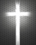 Lights in the shape of a Christian cross. White light in the form of a Christian cross passing through a white brick wall stock photo
