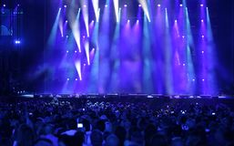 Lights on the stage at stadium with many peopple. Many lights on the stage at stadium during live concert with many peopple stock image
