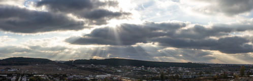 The lights of a sun. Panoramic landscape with clouds, forest on the horizon and the sun`s rays Stock Photos
