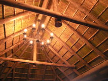 Lights in thatch roof. Chandelier with 6 lights hanging under thatch roof royalty free stock photo