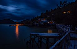 Lights and tones on the catwalks of Caleta Tortel. Photograph of the night landscape of Caleta Tortel, with its tone and lights, from its cypress walkways of stock photography